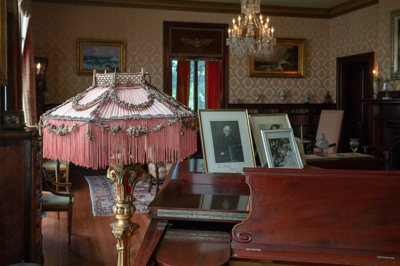 The fringed silk lampshade next to the piano in the drawing room