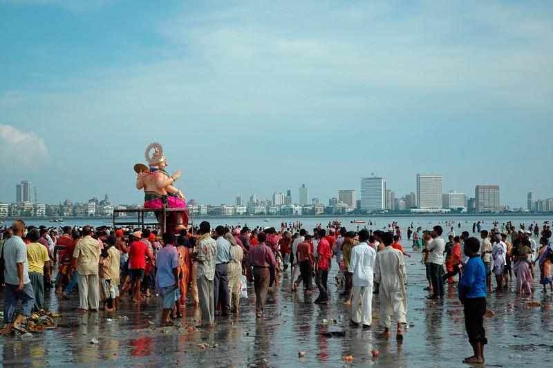 Ganapati Visarjan into the Arabian Sea at Chowpatty Beach with Nariman Point at the backdrop in Mumbai (Bombay), Maharashtra, India. This Hindu festival has lakhs of devotees carrying Lord Ganesha to the sea and immersing the idol.