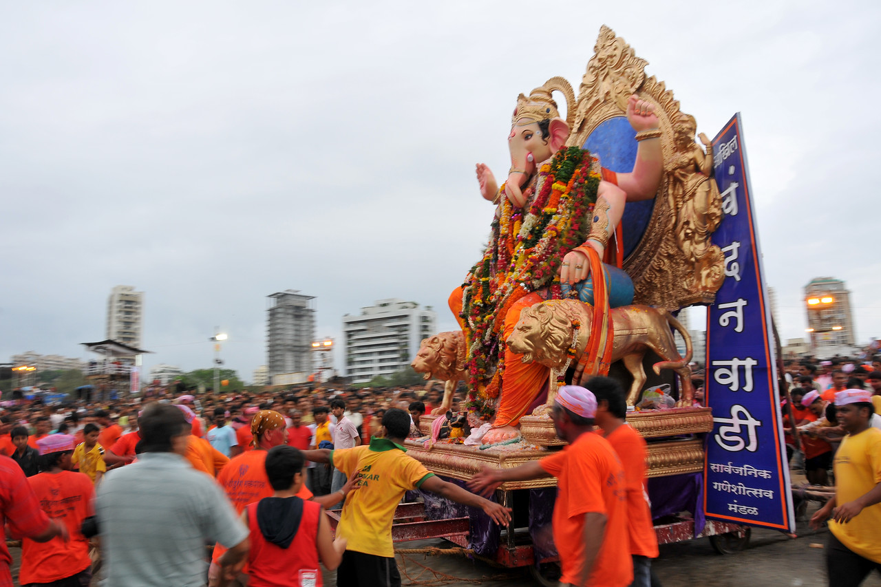 Fast paced movement towards the sea. Small to giant idols of elephant-headed Hindu God Ganesha being taken to Chowpatty beach, Arabian sea in Mumbai, with dancing, beating of drums and grand celebrations for the Ganesh Chaturti festival.