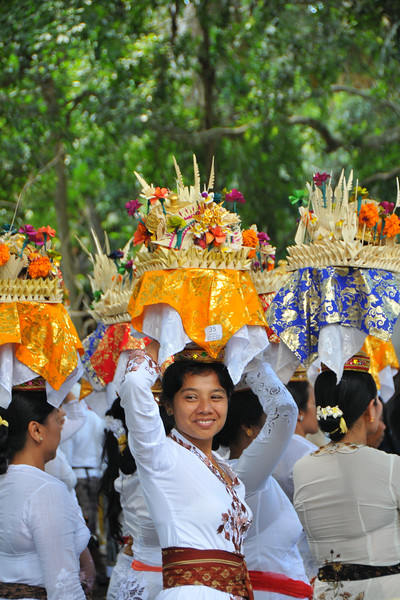 Women carrying offerings on their head at the ceremony taking place in Dalem Agung Padantegal Temple, Sacred Monkey Forest, Ubud.<br /> The vast majority of the Balinese follow one religion - A Shivaite sect of Hinduism that is mixed with pre-Hindu mythologies. The Balinese from before the third wave of immigration, known as the Bali Aga, are mostly not followers of the Balinese Shivaite Hinduism, but their own animist traditions.<br /> <br /> Bali is an Indonesian island with the provincial capital at Denpasar. Lying between Java to the west and Lombok to the east, the island is home to the largest tourist destination in the country and is renowned for its highly developed arts, including dance, sculpture, painting, leather, metalworking and music. What's interesting is that while Indonesia has the world's largest Muslim population, on the island of Bali, 93% of the population is Balinese Hindu and one can find Hinduism in each and every aspect of the life and living.