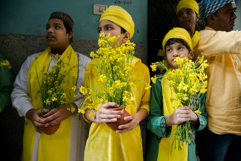 Dressed in yellow and mustard flowers in their hands, young Qwalli singer awaits for the seniors' arrival.