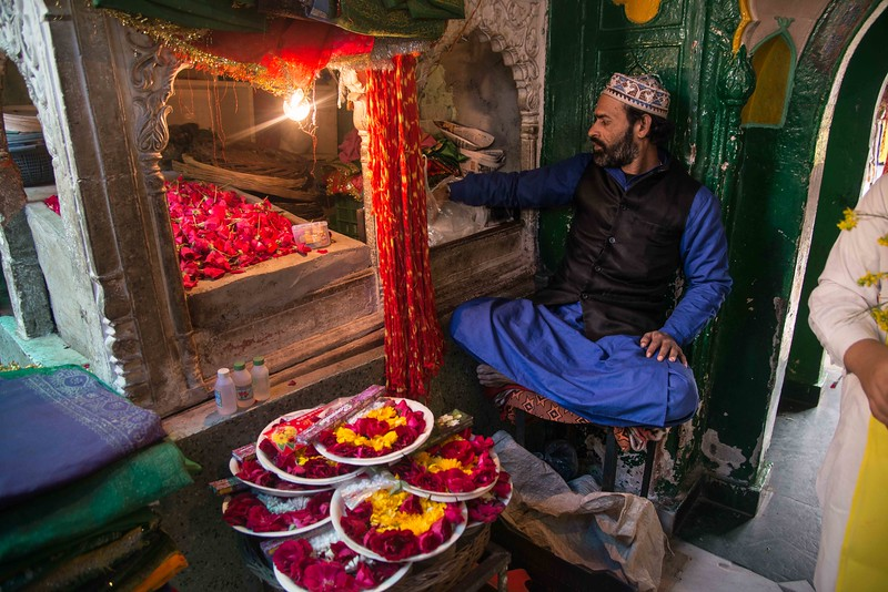 A trader neighbouring Darga is selling chaddar and flowers for the devotees