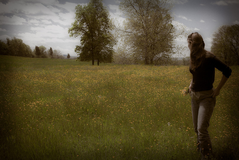 Girl walking in a field picking flowers