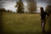 Girl walking in a field picking flowers