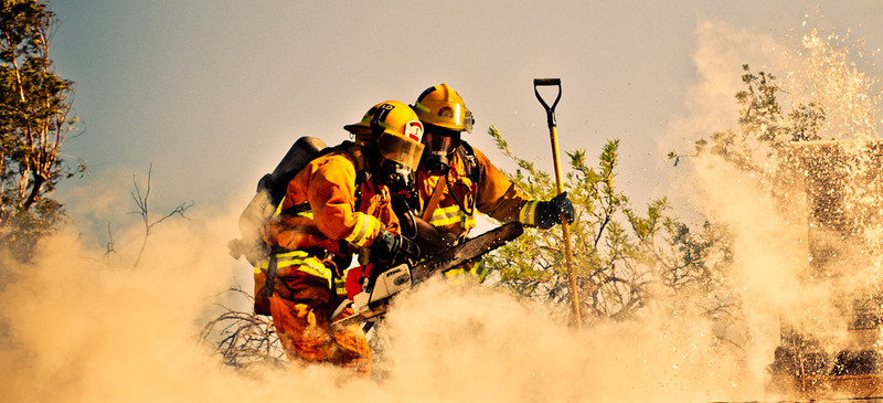 Tucson Fire Department firefighters on the roof of a burning home. 2012.