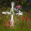 Roadside memorial with cross on Texas State Highway 105, with Indian Paintbrush wildflowers.