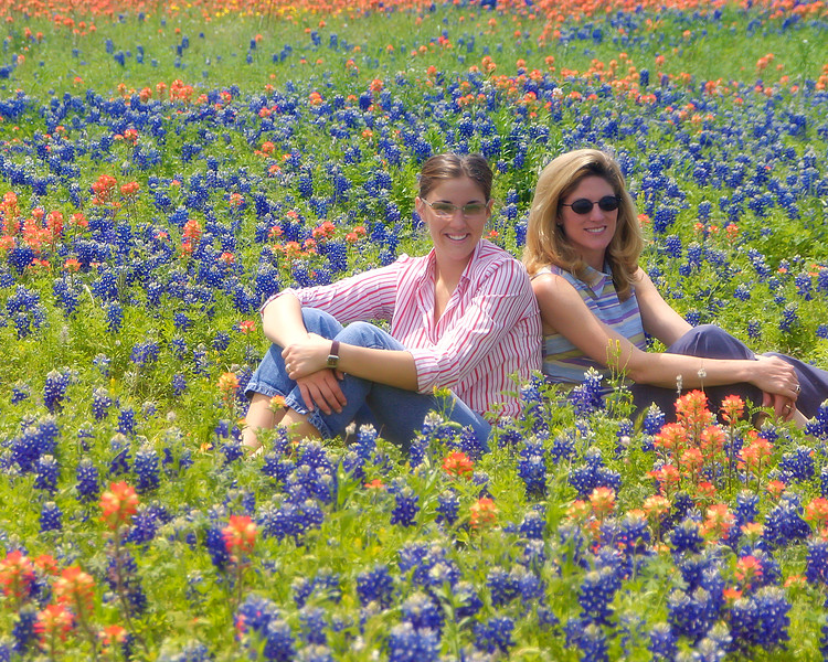 Beehler family enjoying field of bluebonnets and indian paintbrush wildflowers at Brenham, Texas.