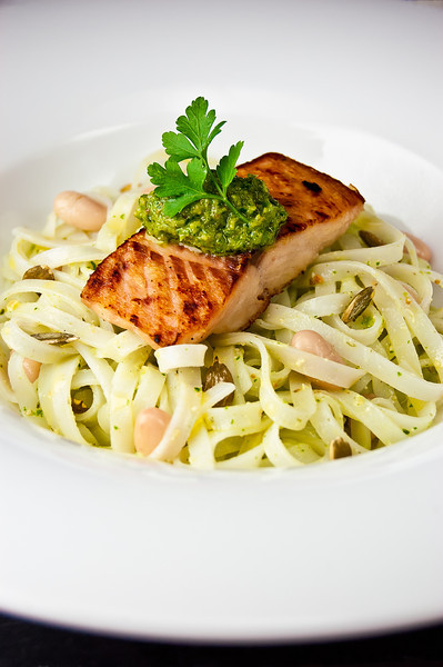 Seared salmon fillet with pumpkin-seeds pesto over rice tagliatelle and white beans