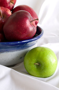 Left Out--a beautiful handmade bowl of red delicious apples with one granny smith left out.
