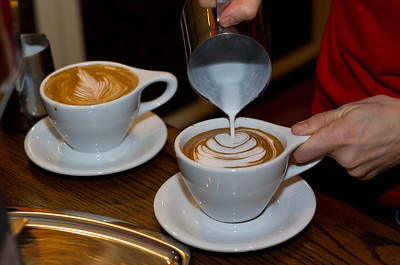 Pouring a design on the top of a latte.