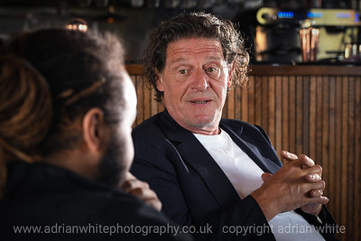 """CELEBRITY CHEF GIVES STUDENTS A TASTE OF CULINARY CAREER  An iconic British chef gave a group of students from Gower College Swansea a sneak peek behind the scenes of his Swansea restaurant along with an insight into his inspiring career.  Marco Pierre White, who last year opened his Steakhouse Bar & Grillat the J-Shed in SA1, met up with five of the College's Catering and Hospitality students.  Mr Pierre White held an informal discussion with the students about his career, the industry and provided invaluable hints and tips of the trade.  With a keen interest in the College's learning programmes, Marco chatted with the students about the College and the ambitions of the students.  """"At the College, we are constantly looking to give our students the very best practical experiences that we can to ensure that they are well prepared for the next stage of their careers,"""" said Mark Jones, Principal at Gower College Swansea. """"Therefore, we are all delighted that some of our Catering and Hospitality students are being given this opportunity to both meet and learn from one of the most well-known and inspirational leaders in this field.""""   Copyright © 2021 by Adrian White  Photography, all rights reserved. For permission to publish - contact me via www.adrianwhitephotography.co.uk Please respect copyright laws."""
