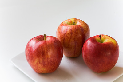 Three ripe, red apples on a square white plate with a white background.