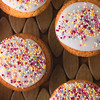 Iced Fairy Cakes on a wooden background