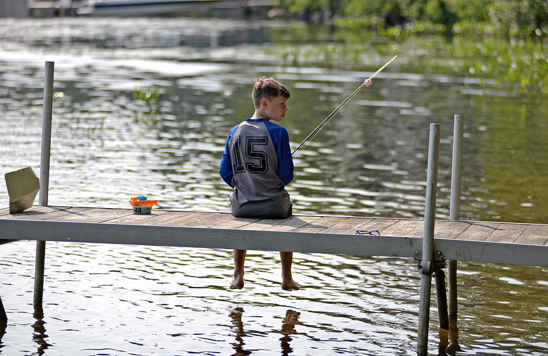 RYAN HUTTON/ Staff photo<br /> Jack Doherty, 9, waits for a bite after casting his line off a dock into Beaver Lake while participating in the Derry Village Rotary Club youth fishing derby on Sunday.