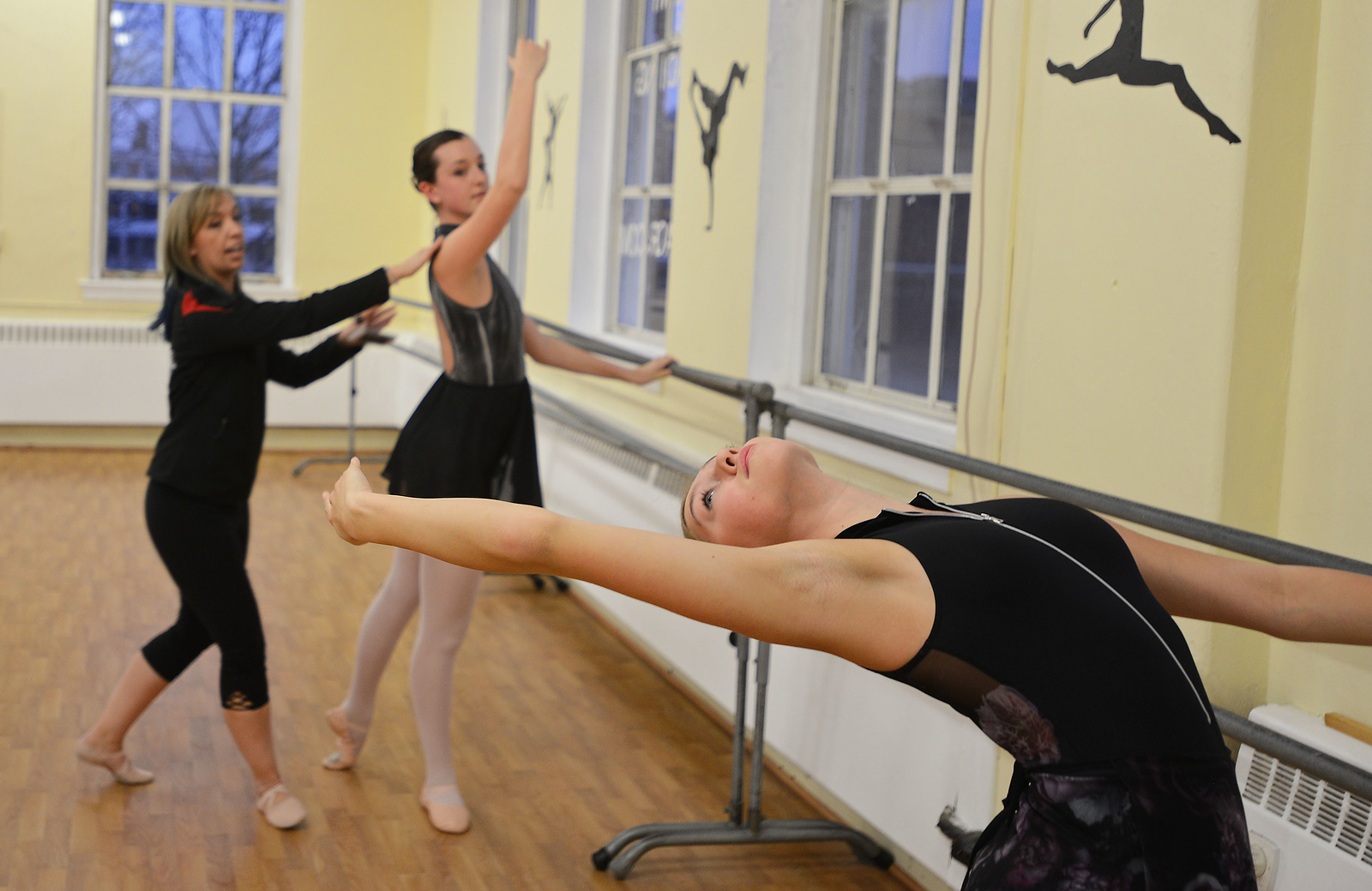 RYAN HUTTON/ Staff photo<br /> Olivia Parziale, 14, leans far back as instructor Erica Schroder helps Caroline Grayson, 14 during ballet practice at the J & D Dance Academy in Reading.