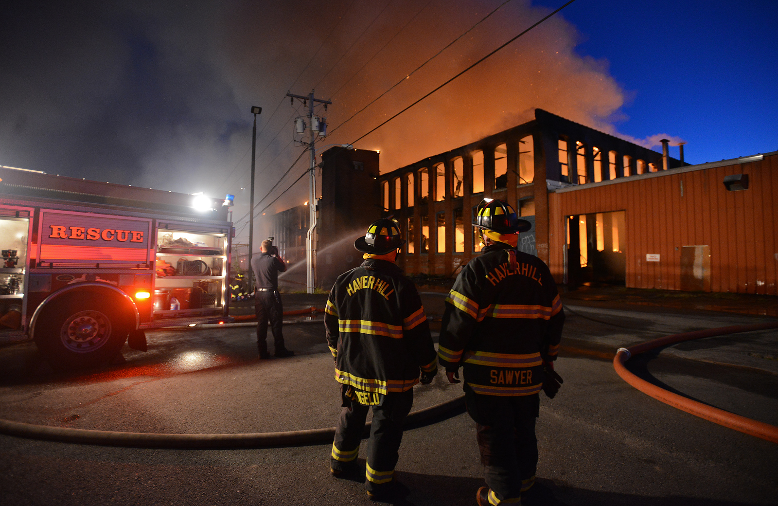 RYAN HUTTON/ Staff photo<br /> Haverhill fire fighters rotate out from fighting the flames still raging in the vacant mill building at 30 Stevens St. on Sunday night.