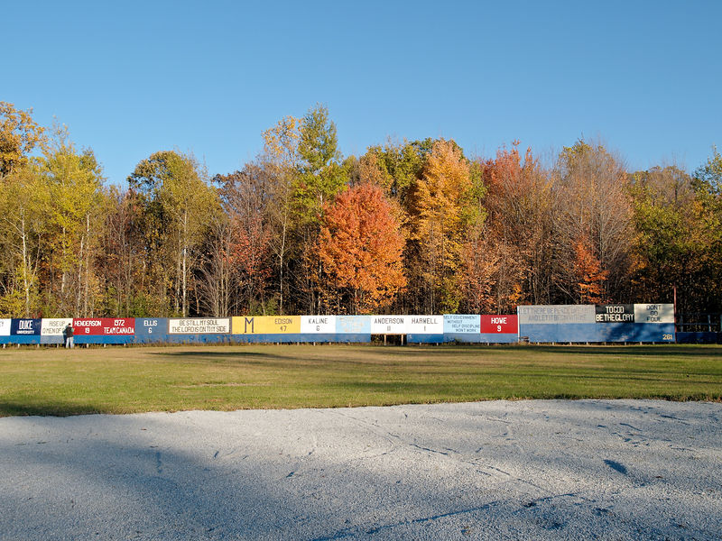 A view of right field from second base.  The changing trees make a great backdrop.  I noticed that what I thought were advertisements are acutally signs with deeper meaning - some are relatives, some are names and numbers of athletes, others are quotes.