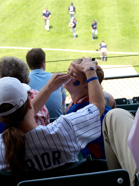 "A young lady getting ""warmed up"" with some face paint before the action starts."