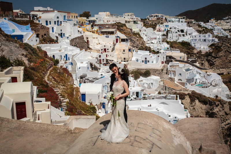 SANTORINI. OIA. IA. CHINESE BRIDE AND GROOM TAKE WEDDING PICTURES. THE CYCLADES. GREECE.