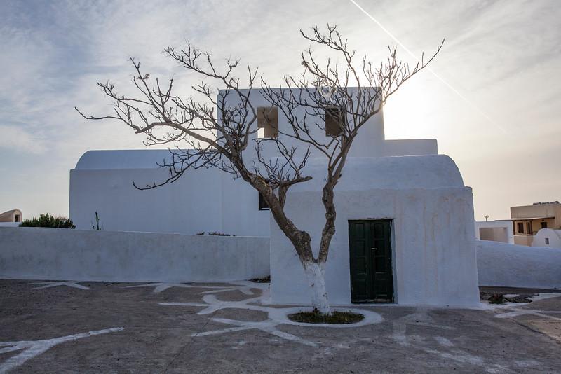 SANTORINI. OIA. IA. WHITE GREEK HOUSE AND TREE.