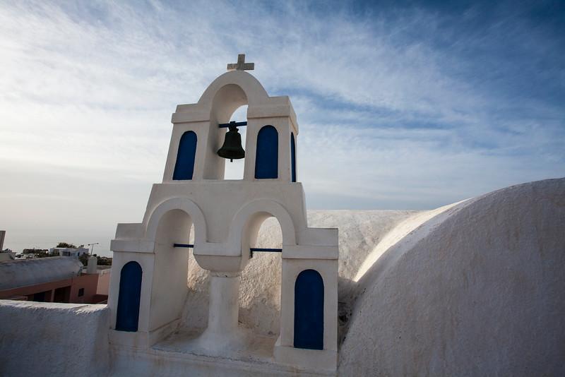 SANTORINI. OIA. IA. WHITE GREEK ORTHODOX CHURCH AND BELL TOWER.