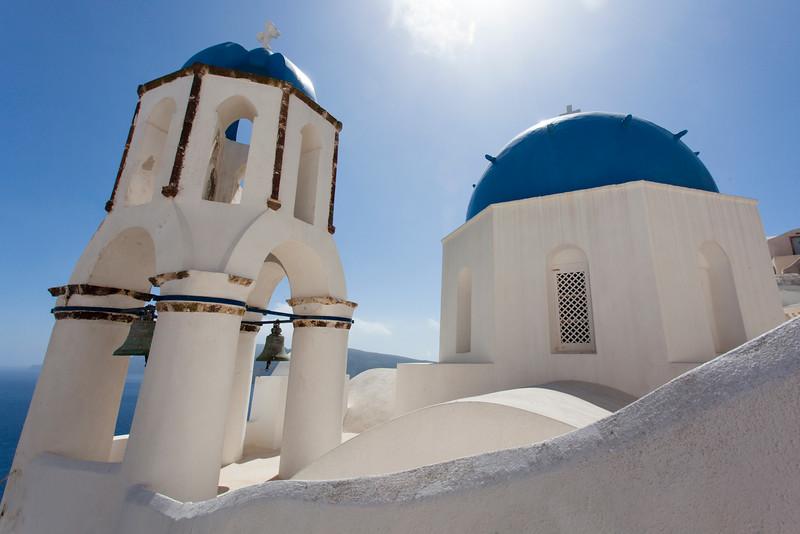 SANTORINI. OIA. IA. WHITE GREEK ORTHODOX CHURCH AND HOUSES ON A CLIFF.
