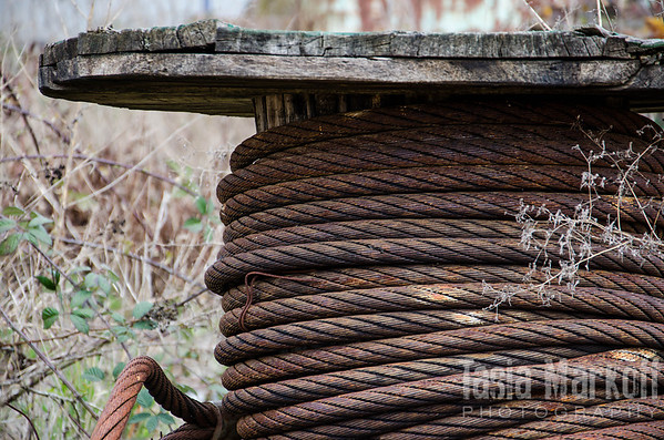 "I don't know what this rope was for but I love the just-slightly-off symmetry of the coiling, the weathered spool, and the incongruousness of thick rusty metal wrapped like thread. The entire thing is about two feet tall and almost as wide. Now it sits in a junkyard in Yamhill. <br /> <br /> Metal print with float mount<br /> 8"" x 12""<br /> $70<br /> <br /> 107"