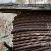 """I don't know what this rope was for but I love the just-slightly-off symmetry of the coiling, the weathered spool, and the incongruousness of thick rusty metal wrapped like thread. The entire thing is about two feet tall and almost as wide. Now it sits in a junkyard in Yamhill. <br /> <br /> Metal print with float mount<br /> 8"""" x 12""""<br /> $70<br /> <br /> 107"""