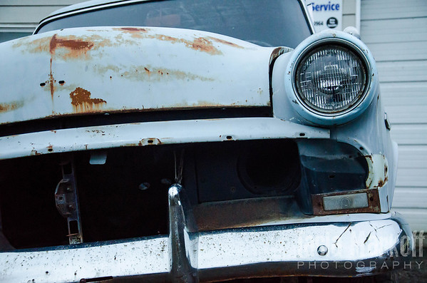 "An old car sits crookedly in a mechanic's lot in Yamhill. I like the contrast of rusty red on pale blue, and how certain parts still look new and shiny while the rest of it is falling apart. <br /> <br /> Fuji Pearl paper on matboard with custom mat and frame<br /> 8"" x 12"" <br /> $345 each<br /> Set of 3 $825<br /> <br /> 137"