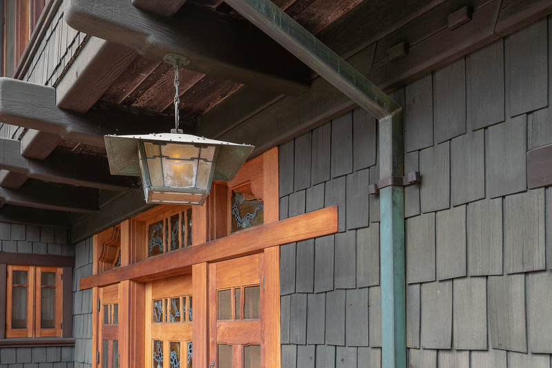 Detail of brass lamp with Gamble House  front doors in the background