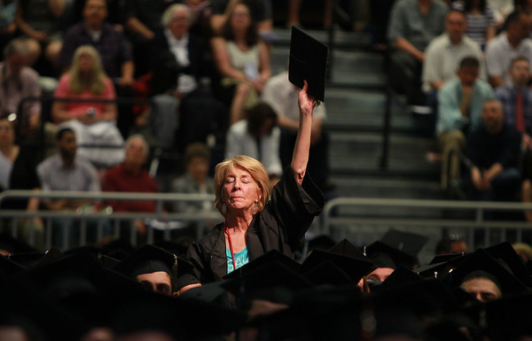 DAVID LE/Staff photo. 5/16/15. Kathryn McKenna, a Salem resident who was diagnosed with ALS earlier this year, stands up, closes her eyes, and raises her mortar board skyward as a quote by Pete Frates is read during the Salem State University Undergraduate Commencement program on Saturday afternoon.