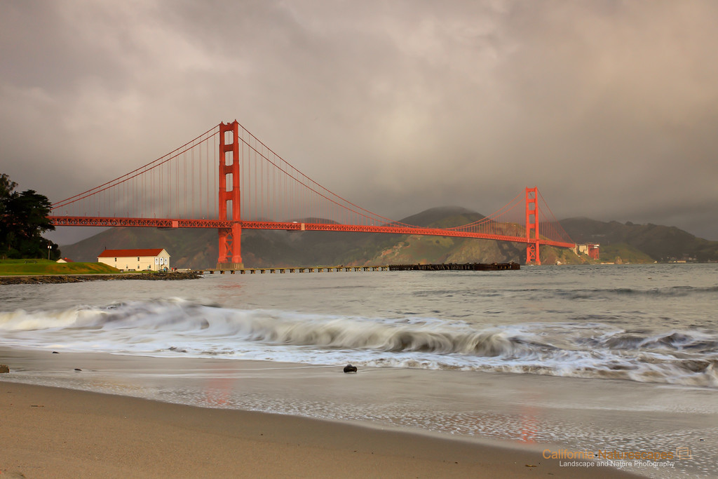 """Golden Gate: A Stormy Day"" <br>Location: Crissy Field, San Francisco, California.  <p><p>Stormy days are often the best to venture out for photography. This day was no exception and I headed to my favorite spot in San Francisco at Crissy Field to shoot Golden Gate bridge in the early morning light. There was a break in the clouds behind me which allowed sun to shine through and lit up the bridge momentarily. The backdrop of dark storm clouds further added to the contrast of the scene. I enjoyed being here for this moment.  <p>Tech Info: <br>Lens: Canon EF 17-40mm f/4L @ 40mm <br>Camera: Canon EOS 5D Mk II <br>Exposure: 1/4sec at f/11 and ISO 400 <br>Filters: LEE ND Grad 0.9"