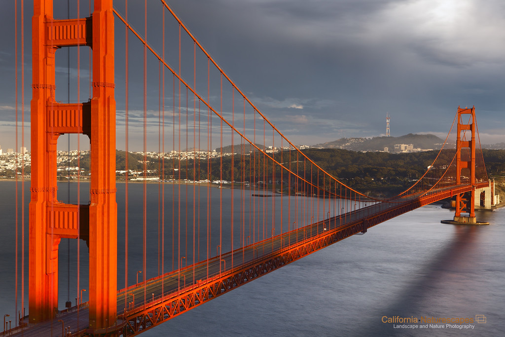 """Sunset Light on Golden Gate"" <br>Location: Golden Gate National Recreation Area, San Francisco, California.  <p><p>It was a beautiful day in the bay and yet there was no one on the bridge!... Well, the truth is that I was witnessing one of the best lighting conditions and wanted to make the best of it from a photographic point of view. So using a long exposure time for this image I blurred all the cars on the bridge making it look empty, reduce distractions and thereby emphasize the beauty of the bridge even more.  <p>Tech Info and Tip: <br>Lens: Canon 24-70 f/2.8L @54mm <br>Camera: Canon 5D Mk II <br>Exposure: 6sec at f/13 and ISO 50 <br>Filters: 2 stop SinghRay ND grad hard edge  <p>The sun is at its northmost location during summer months. This angle of the sun is the best time to obtain light on the bridge you see here. The difficult part is to obtain the clouds to provide a nice background. I was a happy camper after making this image."
