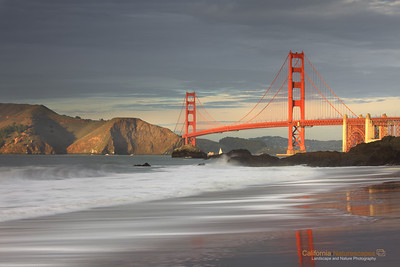 """Winter Light on Golden Gate Bridge"" Location: Baker Beach, San Francisco, California.  Winter brings with it unique opportunity to see the bridge lit up at sunset against the dark storm clouds. Such light is rare and I could manage to click just a few shots before sun went behind the clouds and all contrast in the scene was lost.  Tech Info and Tip: Lens: Canon EF 70-200 f/4L IS @ 78mm Camera: Canon EOS 5D Mk II Exposure: 1.3sec at f/18 and ISO 50 Filters: LEE ND Grads 0.9 soft edge and 0.75 hard edge upside down  There is a hill right behind from where I shot this image and the sun goes behind the hill at sunset thus giving a very short time window in which such light can be obtained on the bridge."