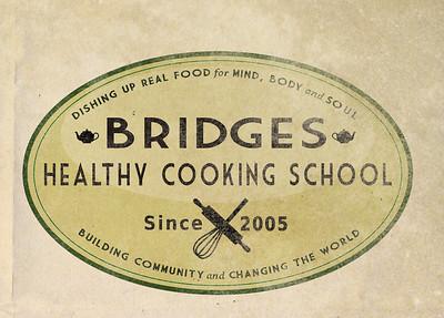 Older, distressed version of the Bridges Healthy Cooking School logo