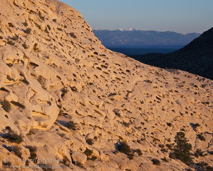 Dawn illuminates the eroded face of Crystal Peak, Mount Moriah in the distance. Western Utah, April 2011.