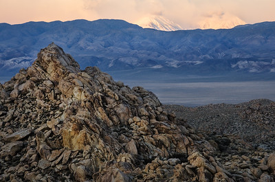 Dawn breaks on the boulders of the Piper Mountain Wilderness and the snowy High Sierra