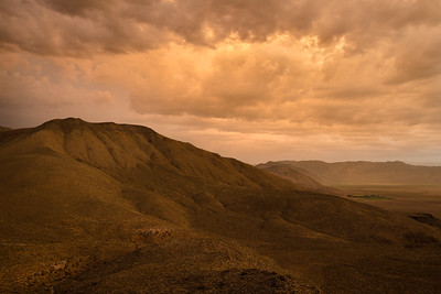 Deep Springs Valley and the Inyo Mountains bathed in gold of a summer monsoon sunset
