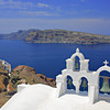Church bells on Santorini island, Greece with a view of the nearby volcano