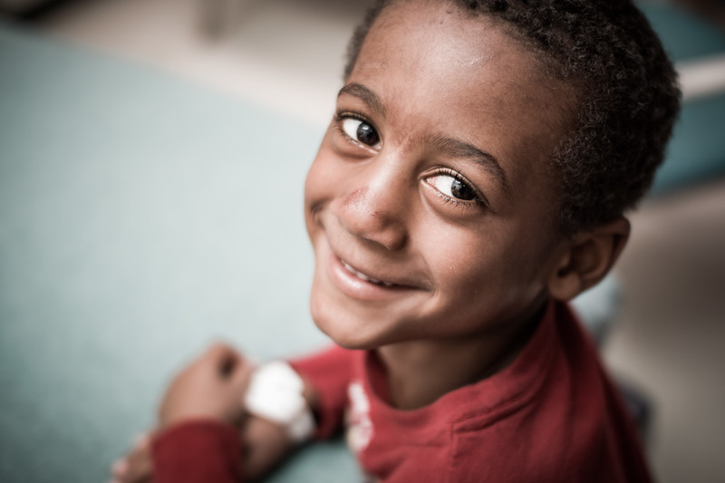 Happy Young Boy Looking into Camera in Waiting Room