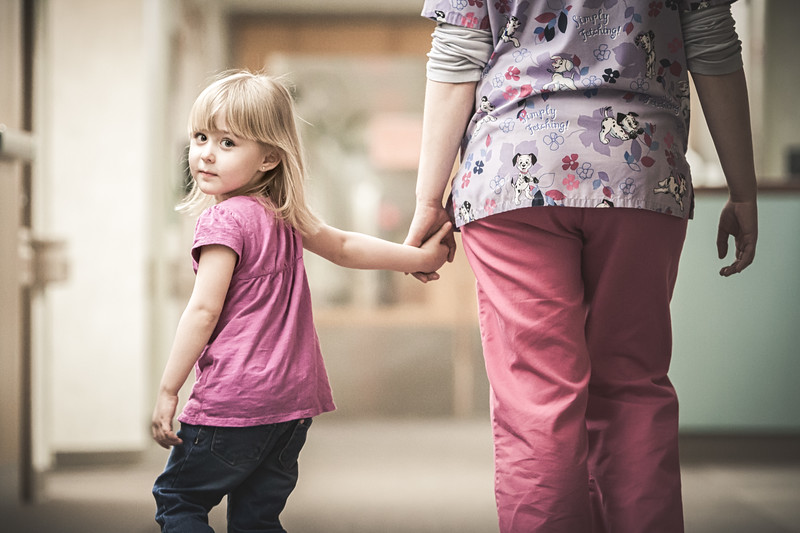 Young Girl Holding Hands with Nurse walking down Hallway