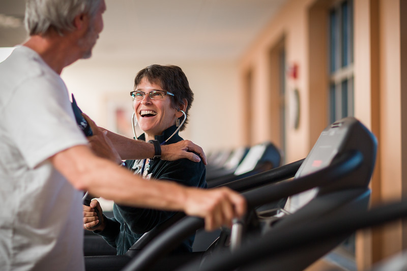 Physical Therapist Smiling While Taking Blood Pressure of Patient on Treadmill