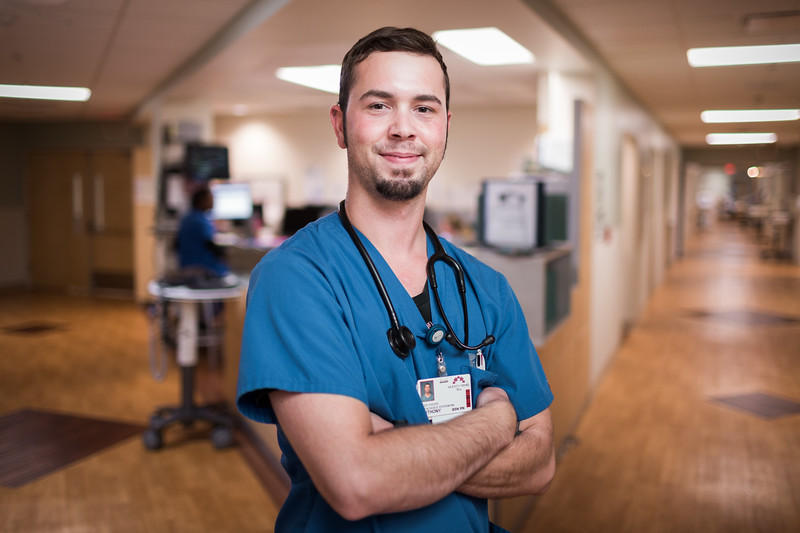 portrait of male nurse near nurses station