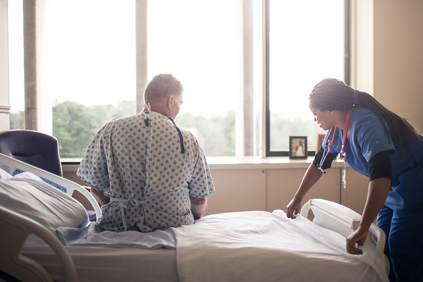 Pleasant Nurse Changing Linens for Patient