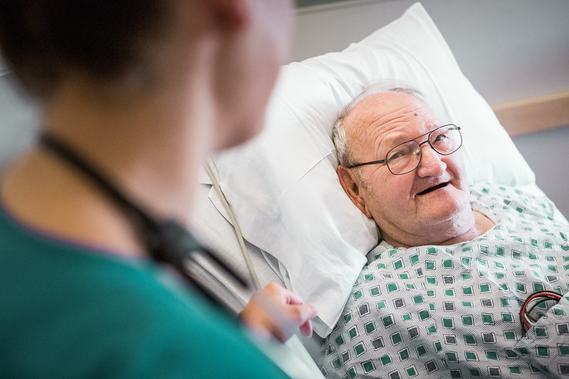 Senior Patient Lying in Hospital Bed Smiling at Nurse