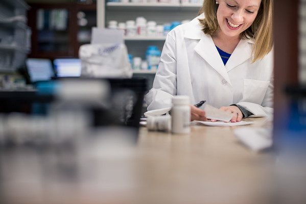 Pharmacist Smiling While Filling Prescription Label