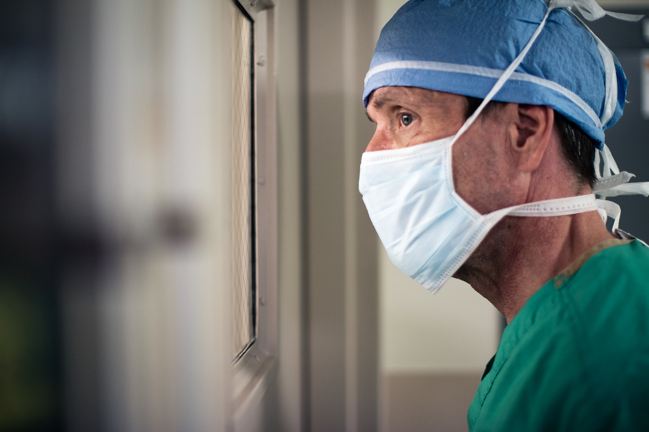 Concerned Surgeon Looking Through Surgical Bay Window