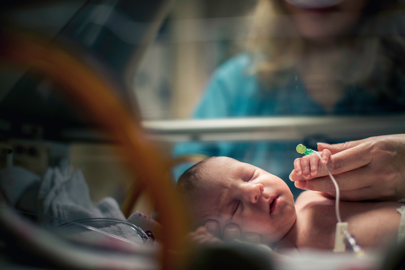 Nurse Comforting Premature Baby in Incubator