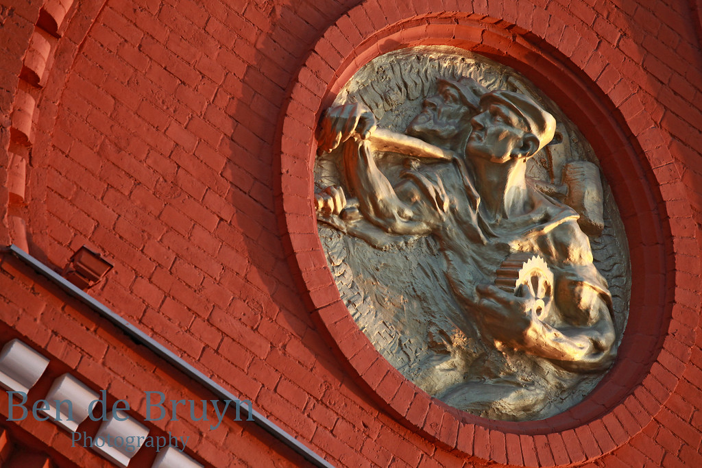 Red brick wall with golden painted sculpture of worker at state historical museum in Moscow Russia on a sunny day