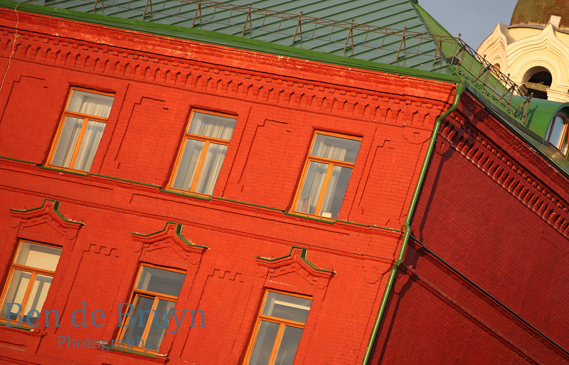 Traditional red clay brick building with green roof covered in late afternoon sunlight in Moscow Russia
